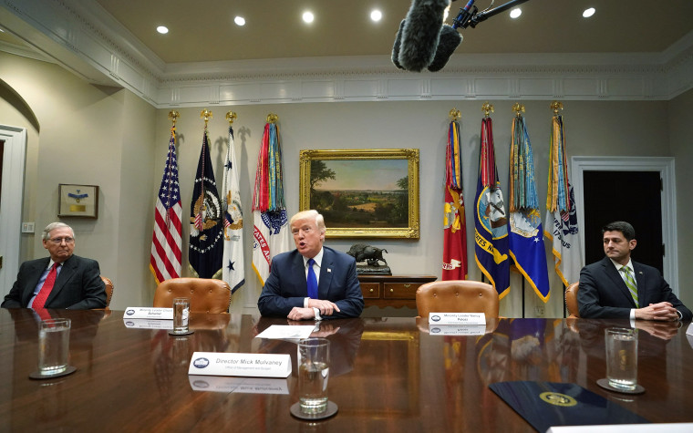 U.S. President Donald Trump speaks to the media as Senate Majority Leader Mitch McConnell (L), R-KY, and Speaker of the House Paul Ryan, R-WI, look on during a meeting with congressional leadership in the Roosevelt Room at the White House on November 28,