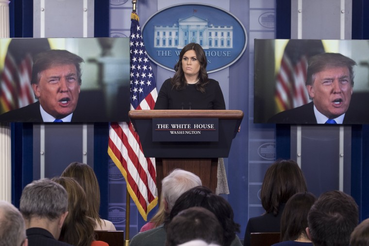 White House Press Secretary Sarah Huckabee Sanders stands beside monitors showing US President Donald J. Trump delivering a statement on the economy, at the beginning of a news conference in the James Brady Press Briefing Room of the White House, January