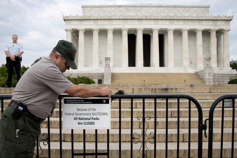 US Park Police officer watches at left as a National Park Service employee posts a sign on a barricade closing access to the Lincoln Memorial in Washington, on Oct. 1, 2013
