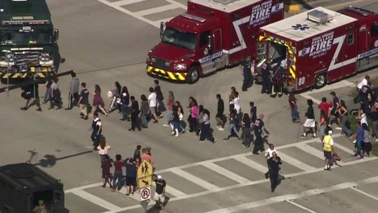Image: Students are evacuated from Marjory Stoneman Douglas High School during a shooting incident in Parkland