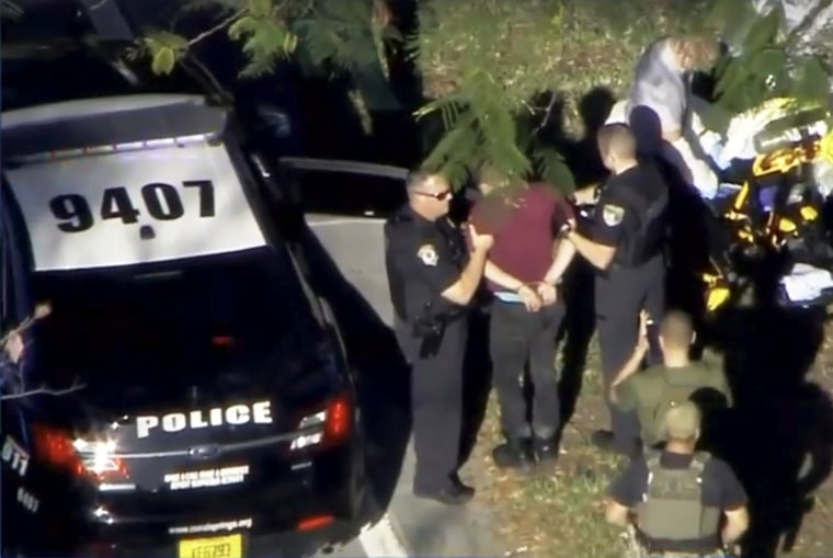 Image: A man placed in handcuffs is led by police near Marjory Stoneman Douglas High School following a shooting incident in Parkland
