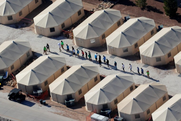 """Image: Immigrant children now housed in a tent encampment under the new \""""zero tolerance\"""" policy by the Trump administration are shown walking in single file at the facility near the Mexican border in Tornillo, Texas"""