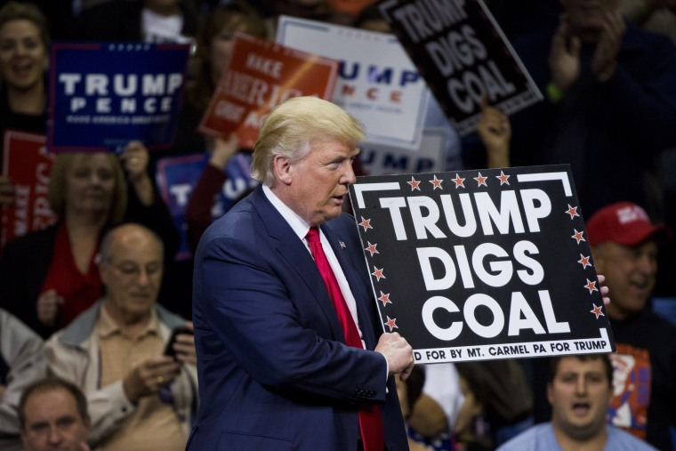 Republican presidential nominee Donald Trump holds a sign supporting coal during a rally at Mohegan Sun Arena in Wilkes-Barre, Pennsylvania on October 10, 2016.