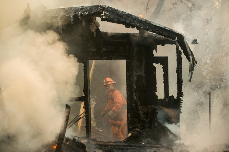 An inmate firefighter examines a burning structure while battling the Loma fire near Morgan Hill, Calif., on Wednesday, Sept. 28, 2016.