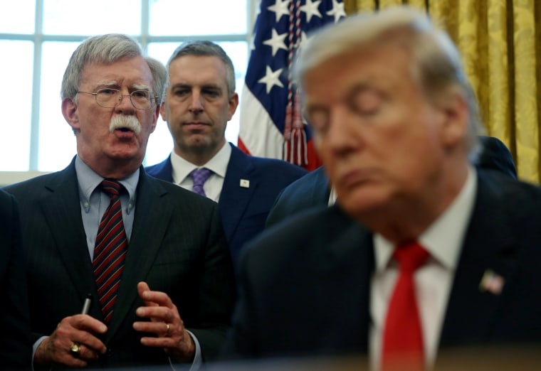 """U.S. President Donald Trump listens as his national security adviser John Bolton speaks during a presidential memorandum signing for the """"Women's Global Development and Prosperity"""" initiative in the Oval Office at the White House in Washington, U.S., Febr"""