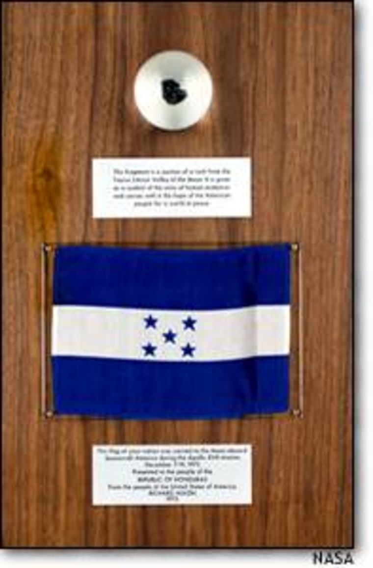 A chip from an Apollo-17 moon rock is mounted on a plaque with the Honduras flag in this image taken at the time of the original presentation.