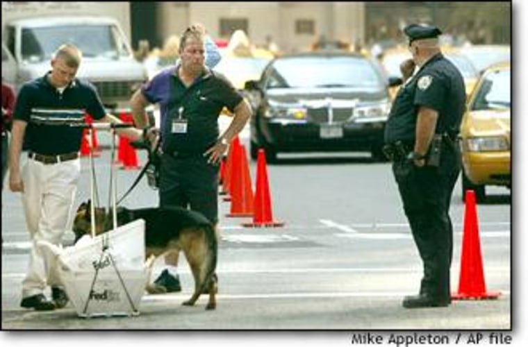 A Secret Service officer uses a bomb-sniffing dog to search a deliveryman's packages outside the Waldorf-Astoria Hotel in New York as President Bush met world leaders on Wednesday.