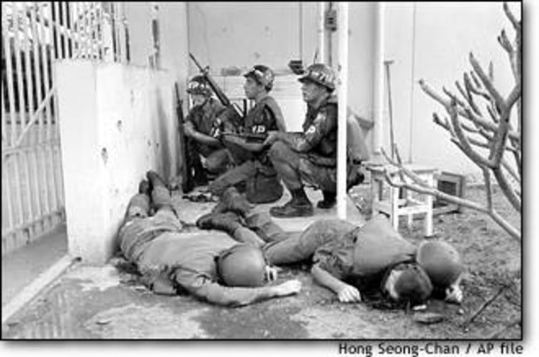 U.S. military police, dead colleagues at their side, take cover at the entrance to the U.S. Embassy in Saigon on the first day of the Tet Offensive, Jan. 31, 1968.