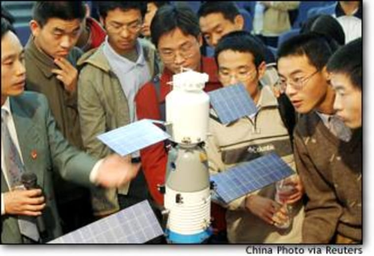 Chinese university students look at a model of the Shenzhou 5 spacecraft in Xian, the capital of China's central province of Shaanxi.