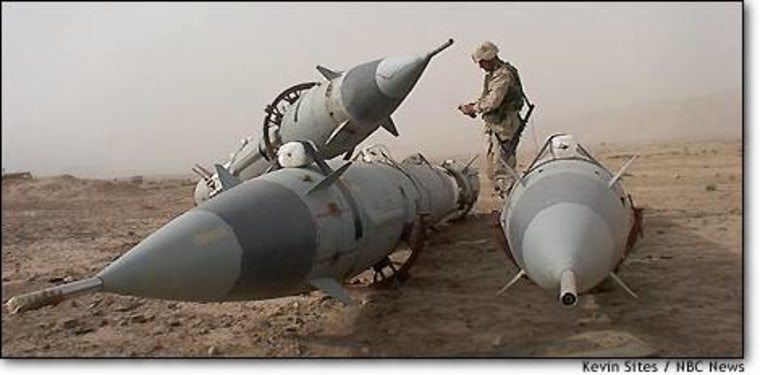 A U.S. combat engineer prepares to destroy these Russian-made SA2 surface-to-air missiles in the desert near Baji.