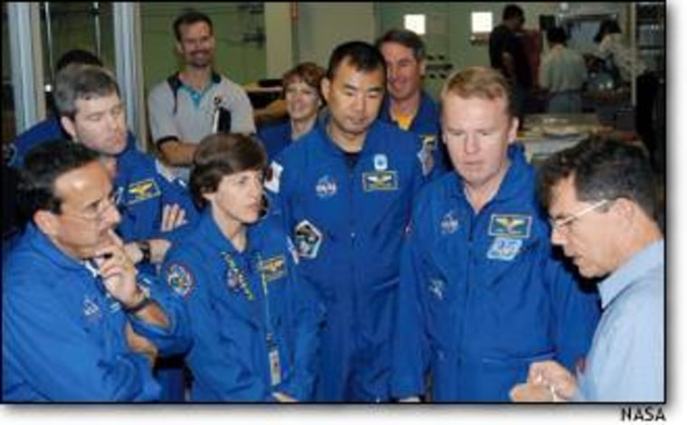 Wearing blue flight suits, astronauts listen to manager Jeff Andress. From left are Charles Camarda, Stephen Frick, Wendy Lawrence, Eileen Collins, Soichi Noguchi, Stephen Robinson and Andrew Thomas. All but Frick are to fly on STS-114, along with James Kelly (not pictured).