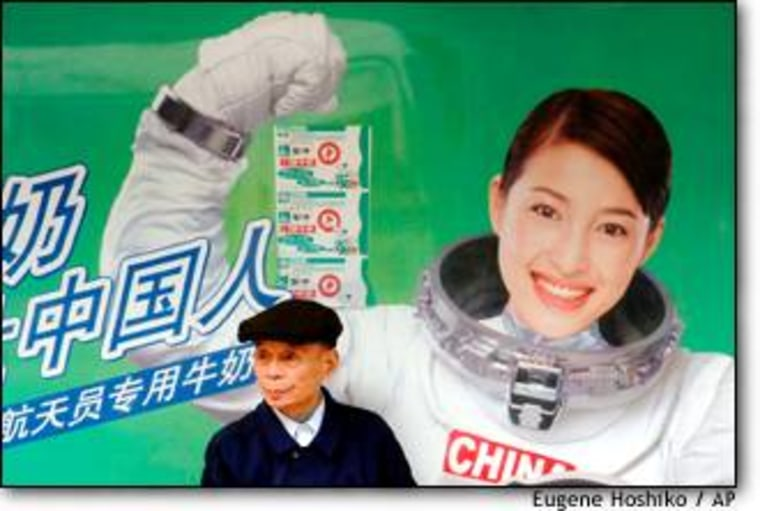"""An elderly Shanghai resident sits in front of an advertisement promising that a locally produced outer-space milk will """"fortify the Chinese people."""""""