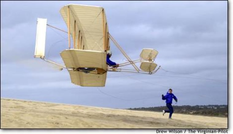 Commercial airline pilot Terry Queijo flies a modified Wright Brothers 1902 glider replica as fellow test pilot Chris Johnson runs alongside at Jockey's Ridge State Park at Nags Head, N.C. The session served as practice for a Dec. 17 re-enactment of the 1903 Wright Flyer's historic outing.