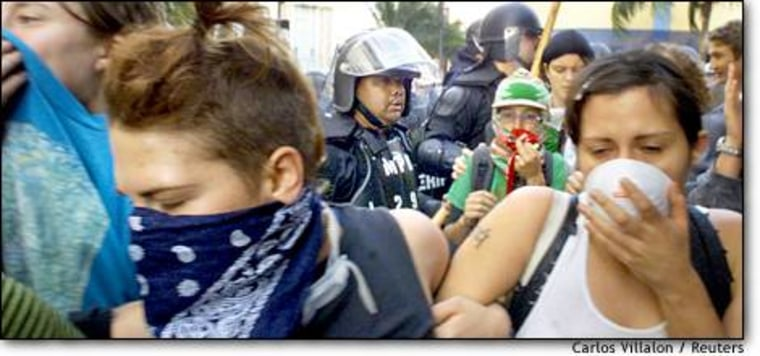 Miami police use pepper spray Thursday to disperse a crowd on Biscayne Boulevard protesting a meeting of the Free Trade Area of the Americas group.