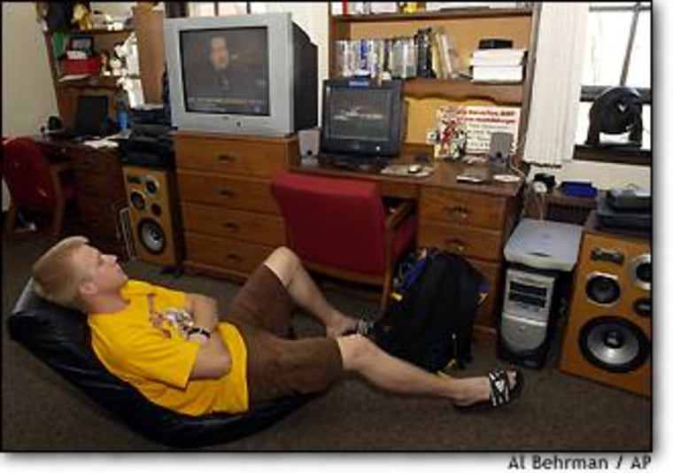 Steve Leslie relaxes in his dorm room at Miami University in Oxford, Ohio, where he uses nine electrical outlets plus two power strips to power his electronic equipment.
