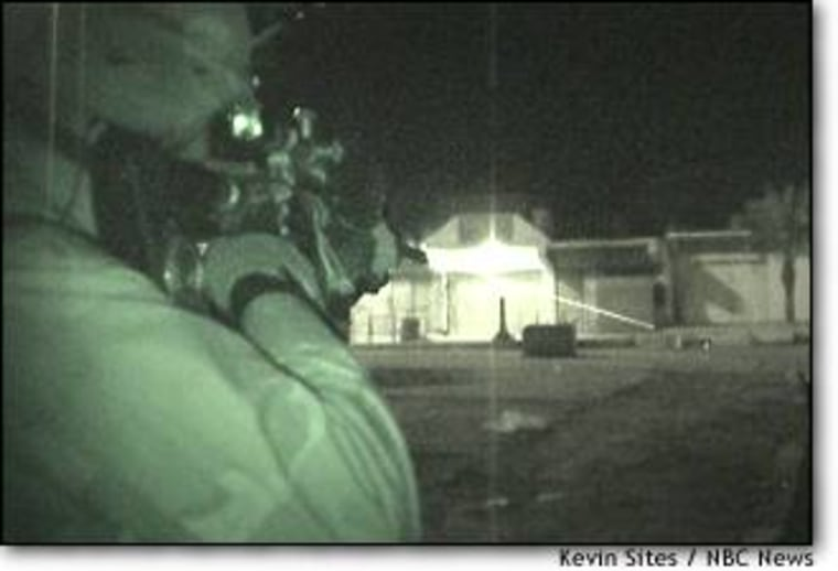 Sgt. Gilbert Nail fires at the IED in Tikrit using an M-16 modified with a laser scope.