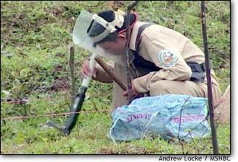 A Vietnamese soldier, trained in the latest de-mining techniques, searches for unexploded bombs and other ordnance in a field outside of Dungha.
