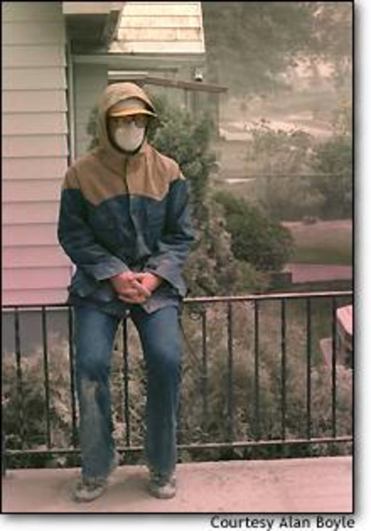 Wearing a face mask to keep his airways clear, Alan Boyle takes a break from sweeping the volcanic ash off his doorstep on May 19, 1980.