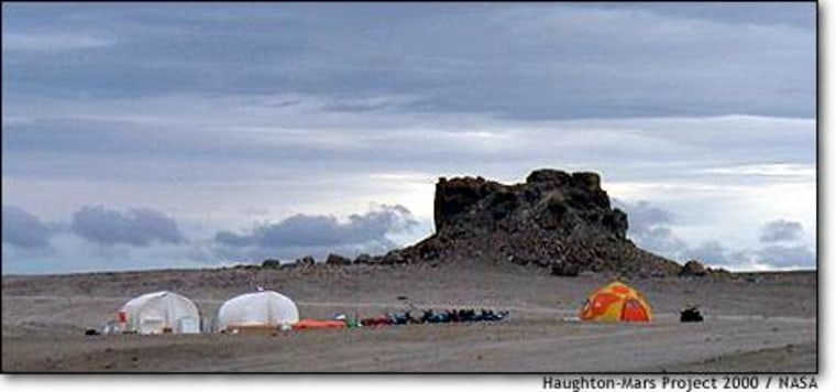 "The tents of the Haughton-Mars Project and the Discovery Channel sprout up on a Marslike landscape in the Canadian Arctic. The rock formation has been dubbed ""the Fortress."""