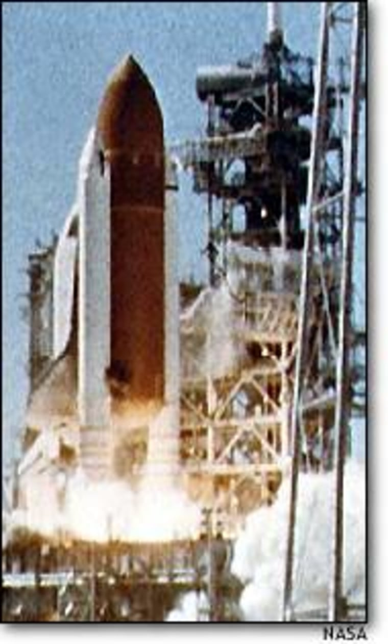 In this image of Challenger's liftoff, a black puff of smoke can be seen issuing from the lower half of a solid rocket booster. The puff was a signal that an insulating O-ring had failed.