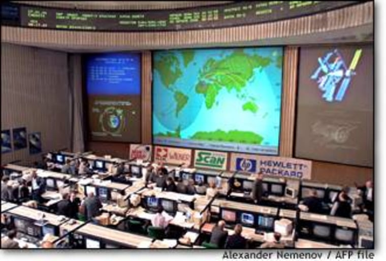 Advertising placards are set up beneath a wall-sized chart showing the Mir space station's path in orbit. In the wake of January's final cargo ship docking, the action has shifted to down the hall to a similar-looking control room for International Space Station Alpha.