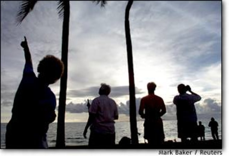 Guests at a resort in Nadi, Fiji watch the evening sky as pieces of the Russian space station Mir race across above their heads during the space station's deorbiting Friday.