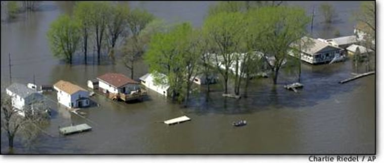 A boat passes by a flooded street at Pleasant Valley, Iowa, during the Mississippi River's rise.