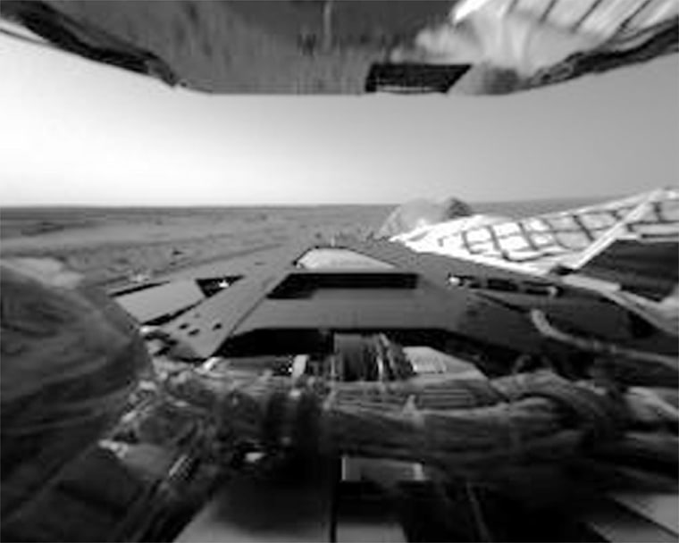 This image shows therover's rear lander petal with a reflection from the bottom of a solar array at the top of the image. The Martian horizon and sky are visible in the background.