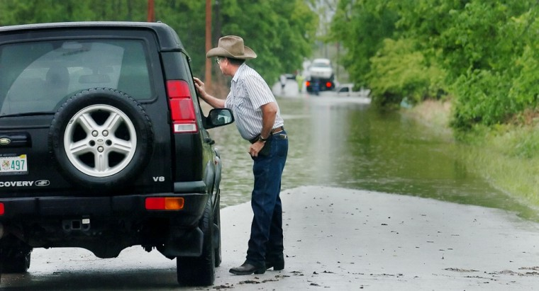 "Wilson Forrest, owner of ""Finally Farm"", talks to a motorist on a flooded road near his property in Broken Arrow, Okla., on Thursday."