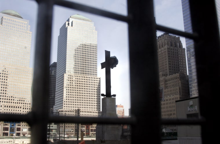 A cross formed by steel beams from the World Trade Center is visible through a fence surrounding Ground Zero in New York in an April 12 file photo.