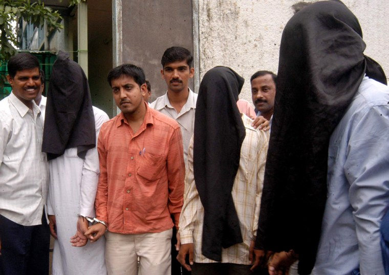 Police officers escort three suspects outside the Anti Terrorist Squad office in Bombay, India, on Friday.