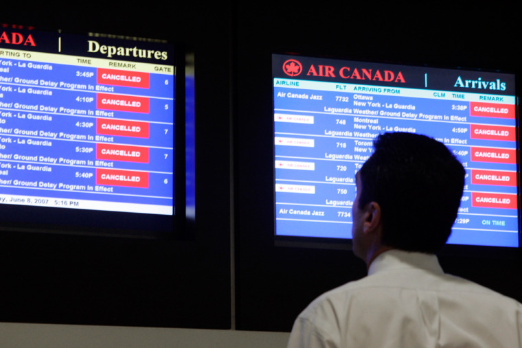 An airline passenger is seen watching for flight delays on monitors at LaGuardia Airport in New York.