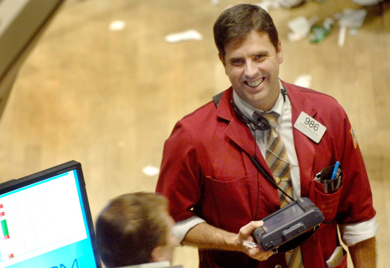 Image: Stephen Guilfoyle of Credit Suisse First Boston smiles as he looks at a monitor