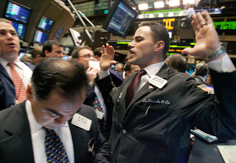 Image: Specialist Jason Hardzewicz, right, calls out prices for AT&T at his post on the floor of the New York Stock Exchange