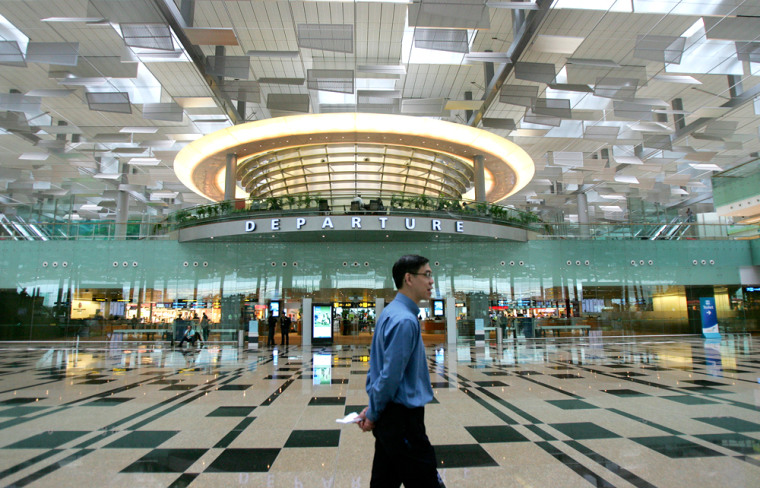 Image: A man walks past the departure gate in Singapore's Changi Airport Terminal 3