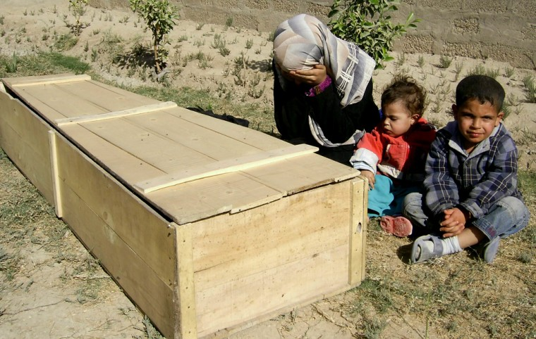 Image: Woman and her children mourn near the coffin of her husband in Baghdad