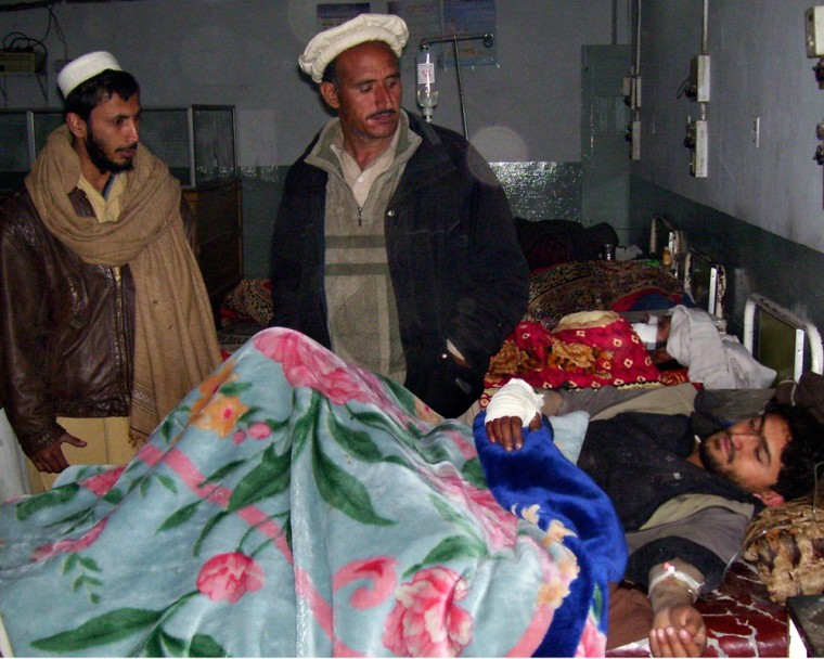 Image: Family members visit an unidentified  injured man following a  suicide attack on a military checkpost, at local hospital in Bannu, Pakistan.