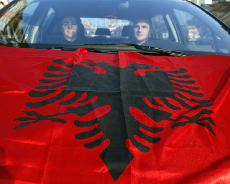 Image: Kosovo Albanians drive a car with Albanian flag on its hood in Pristina