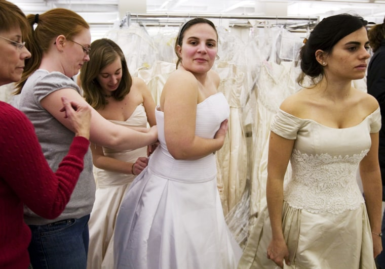 """Image: Rebecca Stamilio, second from right, tries on a wedding gown during the """"Running of the Brides"""" at Filene's Basement in New York"""
