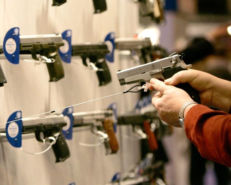 A woman points a handgunat a wall display of other guns.