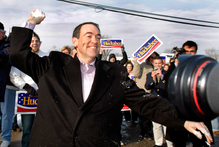 Image: Arkansas Governor and Republican presidential candidate Mike Huckabee throws a snowball at his wife Janet