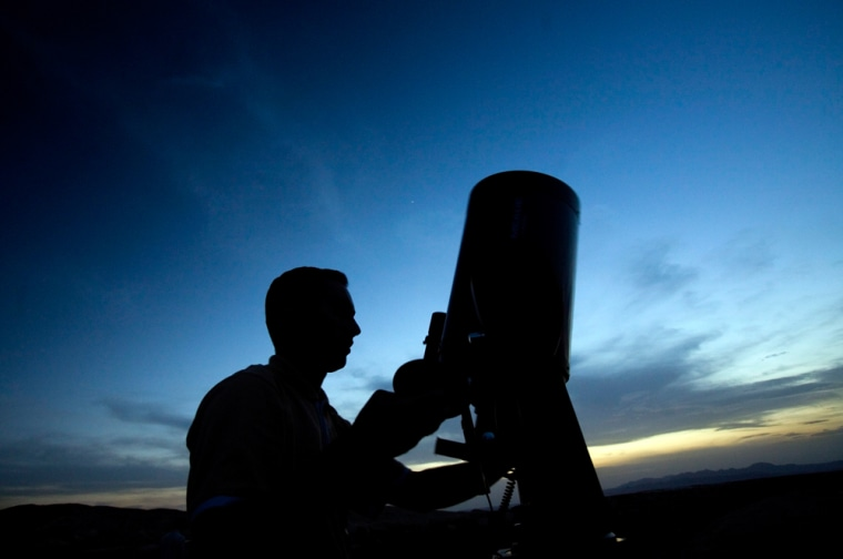 Image: An amateur astronomer sets up a telescope while taking part in the Messier Marathon at Ghasre Bahram in Iran's central desert.