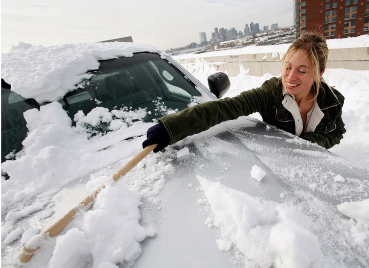 Image: Alicia Montesano, of Arlington, Mass., clears snow from her car at Logan International Airport