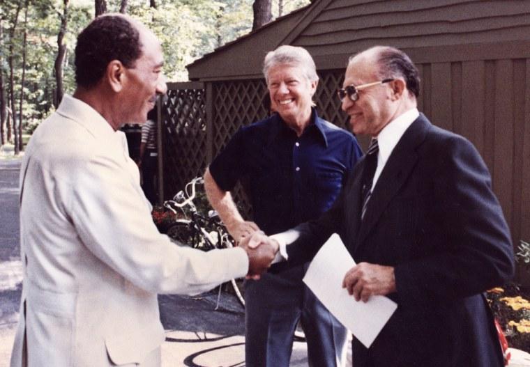 Image: Egyptian President Anwar al-Sadat (l) shakes hands with Israeli Premier Menachem Begin as US President Jimmy Carter looks on.