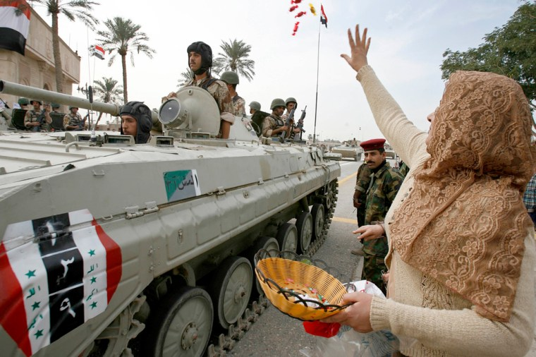 Image: A resident throws sweets towards Iraqi soldiers on a tank during a handover ceremony in Basra