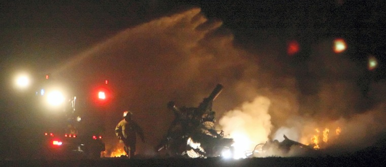 Image: Firefighters battle a fire after a helicopter crash