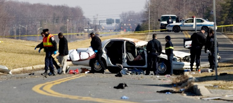 Image: Emergency personnel carry the body of a victim involved in a car crash.