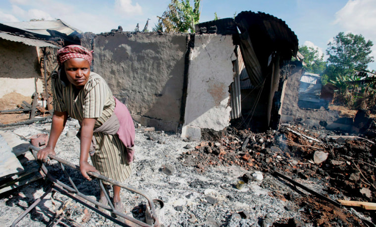 Image: A woman surveys what remains of her home that was torched in the early hours of this morning.