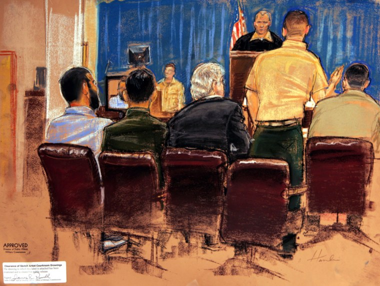 In this photograph of a drawing by AP sketch artist Janet Hamlin, Guantanamoprisoner Omar Khadr, left, sits alongside his defense team, left to right, Muneer Ahmad, Rick Wilson, Marine Lt. Col. Colby Vokey, and Army Capt. John Merriam, as Vokey addresses the robed presiding officer Marine Col. Robert Chester, during a Wednesday hearing at Guantanamo Bay Naval Base, Cuba.