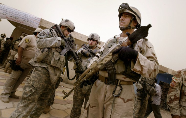 Image:  U.S and Iraqi army soldiers stand guard